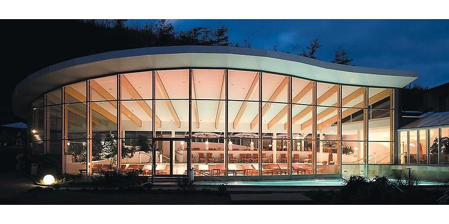 Die Außenansicht des Hallenschwimmbads bei Abend